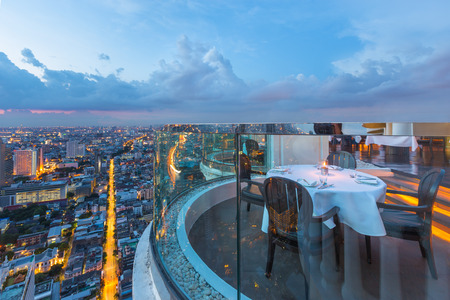 Dining table with beautiful city view at twilight scene 版權商用圖片 - 74515839