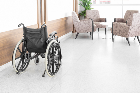 invalidity: Empty wheelchair parked in hospital hallway
