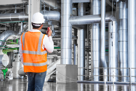 Engineer working in a thermal power plant with talking on the walkie-talkie for controlling work Stock Photo