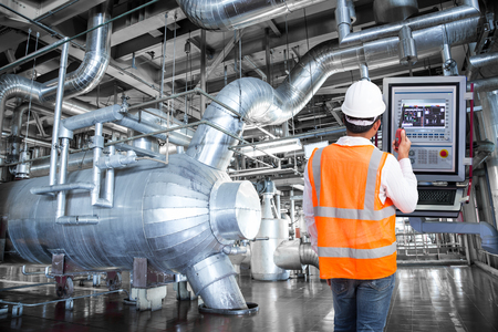 Maintenance engineer looking at monitor control in thermal power plant factory Imagens - 74707878