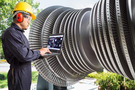Ingenieur, der Laptop-Computer für Wartungsdampfturbine des Wärmekraftwerks verwendet Standard-Bild - 74707890