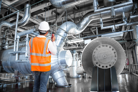 Engineer working in a thermal power plant with talking on the walkie-talkie for controlling work Standard-Bild