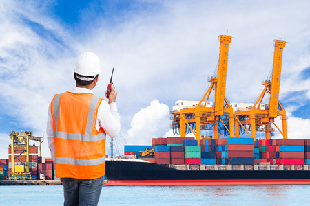 Dock worker talking on the walkie-talkie for controlling loading container in an industrial harbor Stock Photo
