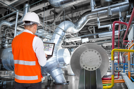 Engineer using laptop computer for maintenance in thermal power plant factory
