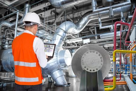 Ingénieur en utilisant un ordinateur portable pour la maintenance dans une usine de centrale thermique