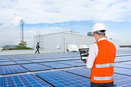 Engineer on factory roof checking solar panels Stockfoto