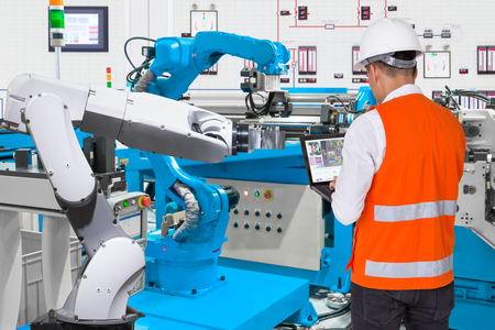 Engineer using laptop computer for maintenance automatic robotic hand machine tool at industrial manufacture factory, Industry 4.0 concept Stock Photo