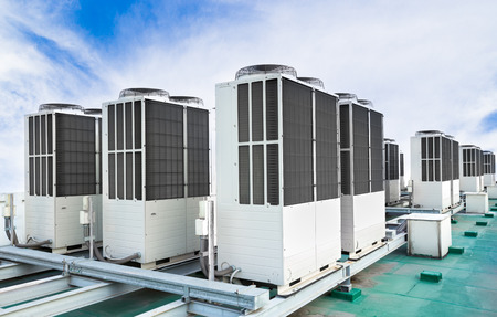 Una fila di unità di condizionamento d'aria sul tetto con il cielo blu Archivio Fotografico - 85978384