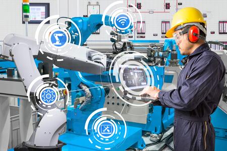 엔지니어 유지 보수를 위해 랩탑 컴퓨터를 사용하는 자동 로봇 손 기계 도구 산업 제조 공장에서 스톡 콘텐츠