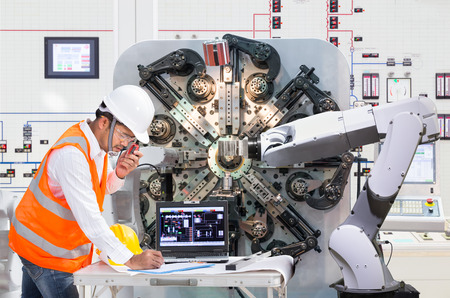 Engineer using laptop computer for maintenance automatic robotic hand machine tool at factory, Industry 4.0 concept