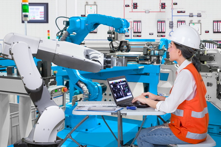 Woman software engineers developing automated robotic in production line, Industry 4.0 concept Standard-Bild