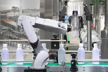 Robotic arm holding water bottles on drink production line in factory, Industry 4.0 concept