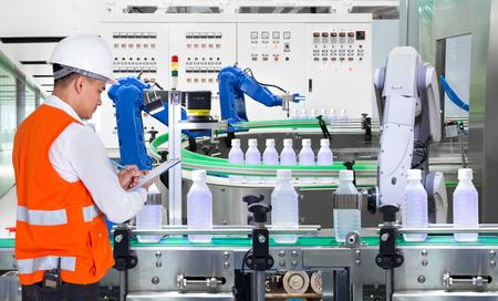 Ingeniero que controla la robótica automatizada en la planta de producción de bebidas de la fábrica.