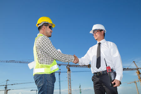 Construction engineer with worker shaking hands at construction site Reklamní fotografie