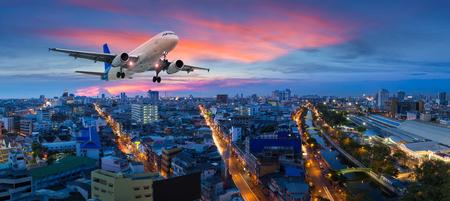 トワイライト シーンでパノラマ都市の飛行機が離陸します。