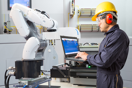 Engineer using laptop computer for maintenance automatic robotic hand machine tool in smart factory, Industry 4.0 concept