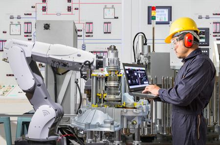 自動車産業における工作機械メンテナンス自動ロボット手のラップトップ コンピューターを使用する技術者