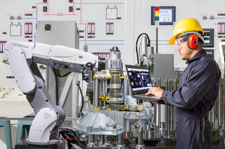 Engineer using laptop computer for maintenance automatic robotic hand machine tool in automotive industry Banque d'images