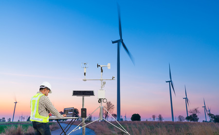 Engineer using laptop computer collect data with meteorological instrument to measure the wind speed, temperature and humidity and solar cell system on wind turbine station, Smart agriculture technology concept