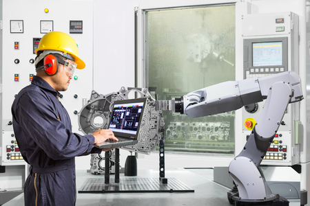 Engineer using laptop computer control automatic robotic hand with CNC machine in automotive industry, Smart factory concept
