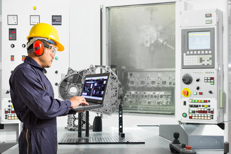 Engineer using laptop computer control automotive CNC machine in automotive industry, Smart factory concept