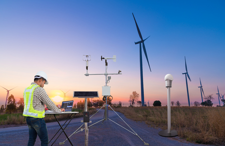 L'ingegnere che utilizza il computer portatile raccoglie dati con lo strumento meteorologico per misurare la velocità del vento, la temperatura e l'umidità e il sistema di celle solari sulla stazione della turbina eolica, concetto di tecnologia agricola intelligente