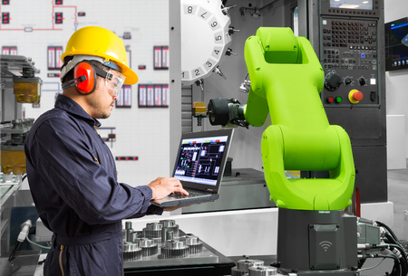 Engineer using laptop computer control automatic robotic hand machine tool with CNC machine in automotive industry, Industry 4.0 concept