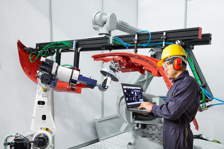 Engineer using laptop computer maintenance robot grip automotive workpiece, Smart factory concept