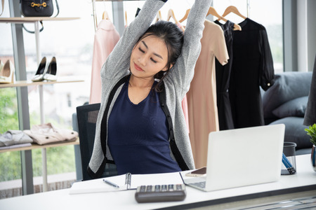 Asian creative designer stretching arms and close eye in front of laptop computer on work desk