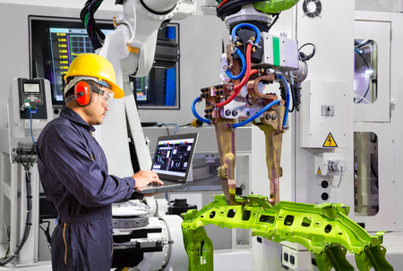 Maintenance engineer using laptop computer control robot grip automotive workpiece in smart factory, Industry 4.0 concept Reklamní fotografie