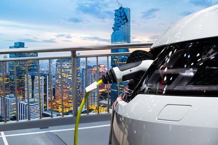 Electric car charging on parking lot of rooftop building