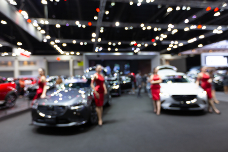 Blurred female presenter with exhibition hall showing cars and automobiles, business commercial event concept Reklamní fotografie