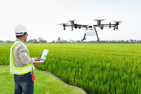 El agricultor técnico usa el drone de la agricultura del control de la computadora wifi volar para rociar fertilizante en los campos de arroz, concepto Smart Farm 4.0