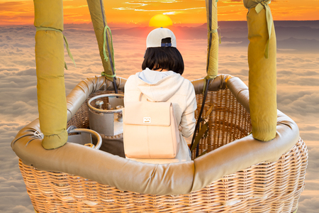 Adventure female traveler looking natural view in basket of hot air balloon over the sea foggy, Adventure concept