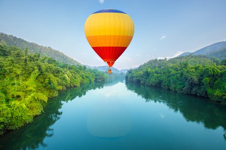 Hot air balloons flying over river