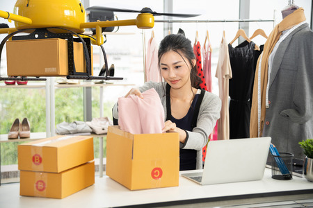 Young asian women packing cloth on box for delivery to customer by air drone, Small business with modern technology shipment innovation and eco concept Reklamní fotografie