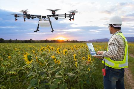 Un agriculteur technicien utilise un drone agricole de contrôle informatique wifi sur le champ de tournesol, concept de ferme intelligente