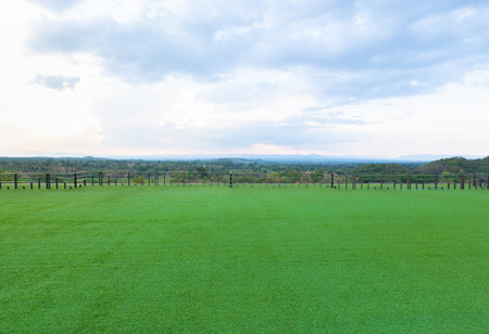 Green artificial grass field on rooftop of hotel with natural view
