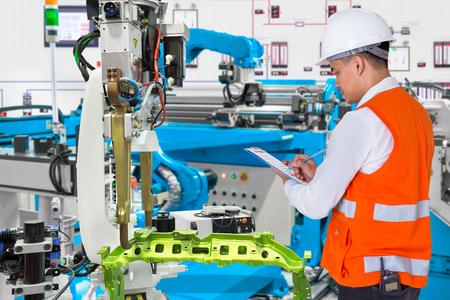 Ingegnere che controlla quotidianamente la manutenzione del robot automobilistico automatizzato nella linea di produzione dell'industria automobilistica Archivio Fotografico