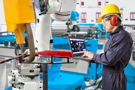 Inżynier używający laptopa do konserwacji robota do chwytania pozycji obrabianego przedmiotu samochodowego, koncepcja inteligentnej fabryki