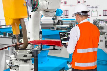 Ingeniero que usa la pieza de trabajo automotriz del agarre del robot del mantenimiento de la computadora portátil, concepto de la industria 4.0