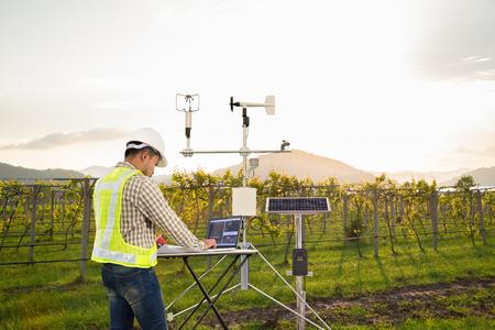 Agronom korzystający z komputera typu tablet zbiera dane za pomocą instrumentu meteorologicznego do pomiaru prędkości wiatru, temperatury i wilgotności oraz systemu ogniw słonecznych w rolniczym polu winogronowym, koncepcja inteligentnej farmy Zdjęcie Seryjne