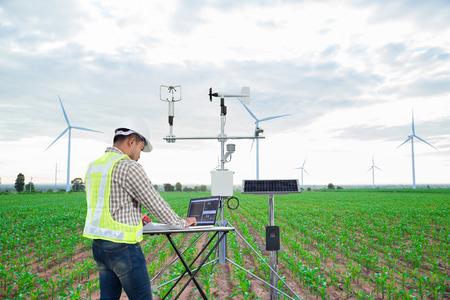 Ingenieur, der einen Tablet-Computer verwendet, sammelt Daten mit einem meteorologischen Instrument, um die Windgeschwindigkeit, Temperatur und Luftfeuchtigkeit sowie das Solarzellensystem auf dem Hintergrund des Maisfeldes zu messen
