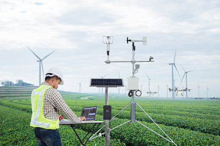Engineer using tablet computer collect data with meteorological instrument to measure the wind speed, temperature and humidity and solar cell system on green tea field, Smart agriculture technology concept Reklamní fotografie