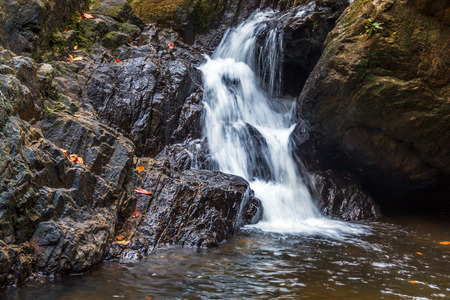 surrounded: Small waterfall surrounded by huge stones Stock Photo