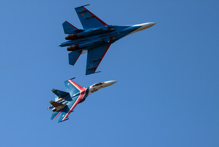 aerobatics: Two heavy fighters Sukhoi Su-27, NATO reporting name: Flanker perform aerobatics over its airbase diring the exhibition Army-2015. They belong to the aerobatic team Russian knights.