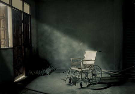Una silla de ruedas de edad en la habitación de edad Foto de archivo
