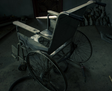 an old wheelchair in old room. old wheelchair was forsaken. this is lonely and scary concept.