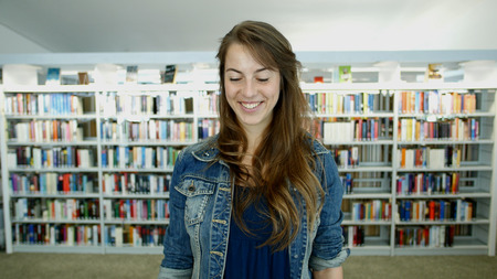 A young woman in a public library. Its her leisure time and she is looking for some good books to read. Stock Photo