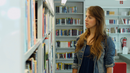 leisure time: A young woman in a public library. Its her leisure time and she is looking for some good books to read. Stock Photo